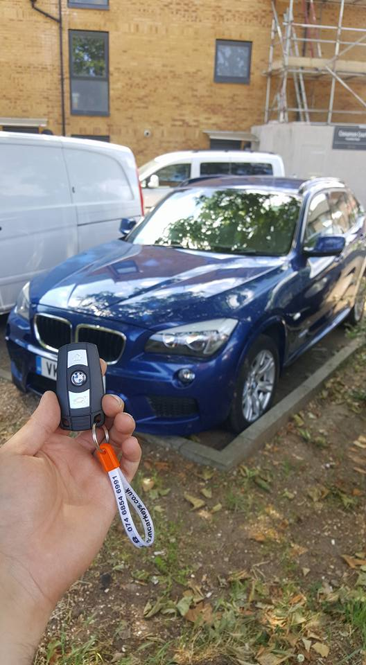 a new key being held up in front of a blue bmw